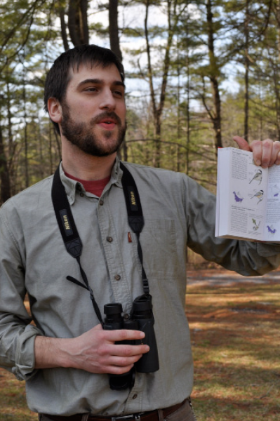 A Shaver's Creek staff member holds a field guide of birds