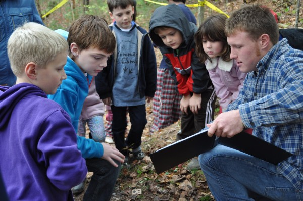 A Penn State student works with a group of young children