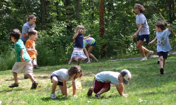 Counselors play an active game with young campers