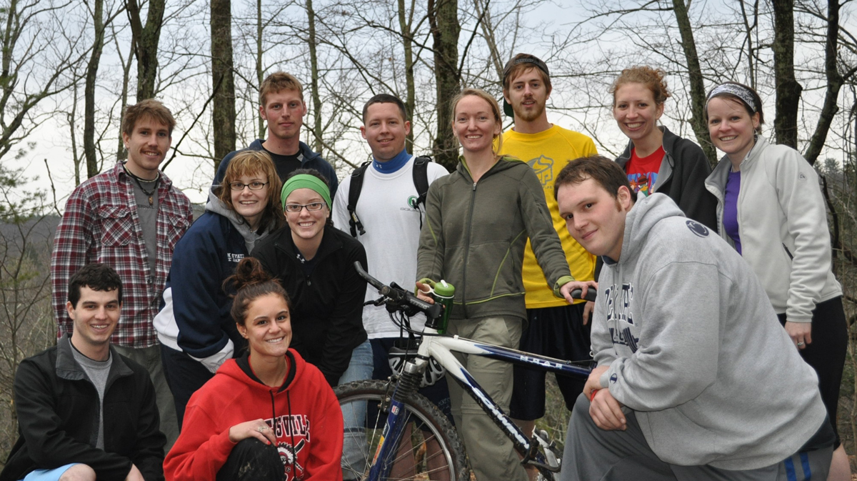A group of Penn State students stand around a bike