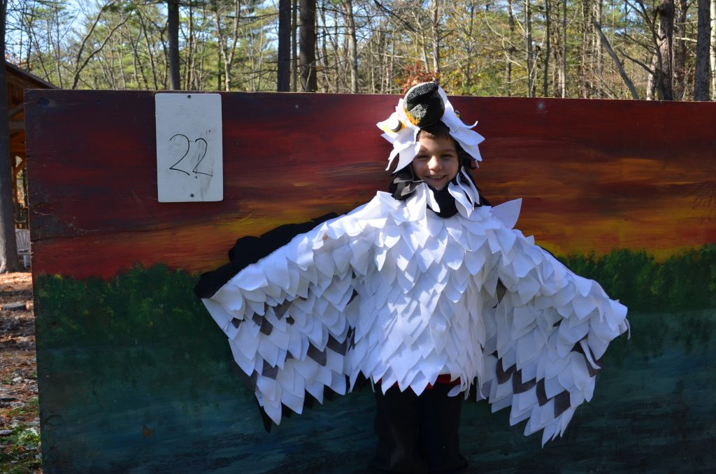 A young boy poses in his white bird costume