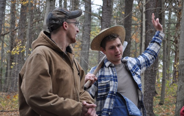 A man in a farmer costume talks to a Fall Harvest visitor