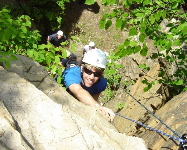 A KINES student climbs a cliff wall