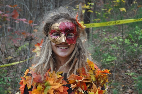 A woman in a mask and a colorful, leafy costume