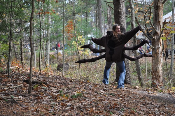 A Penn State student wears a spider costume in the woods
