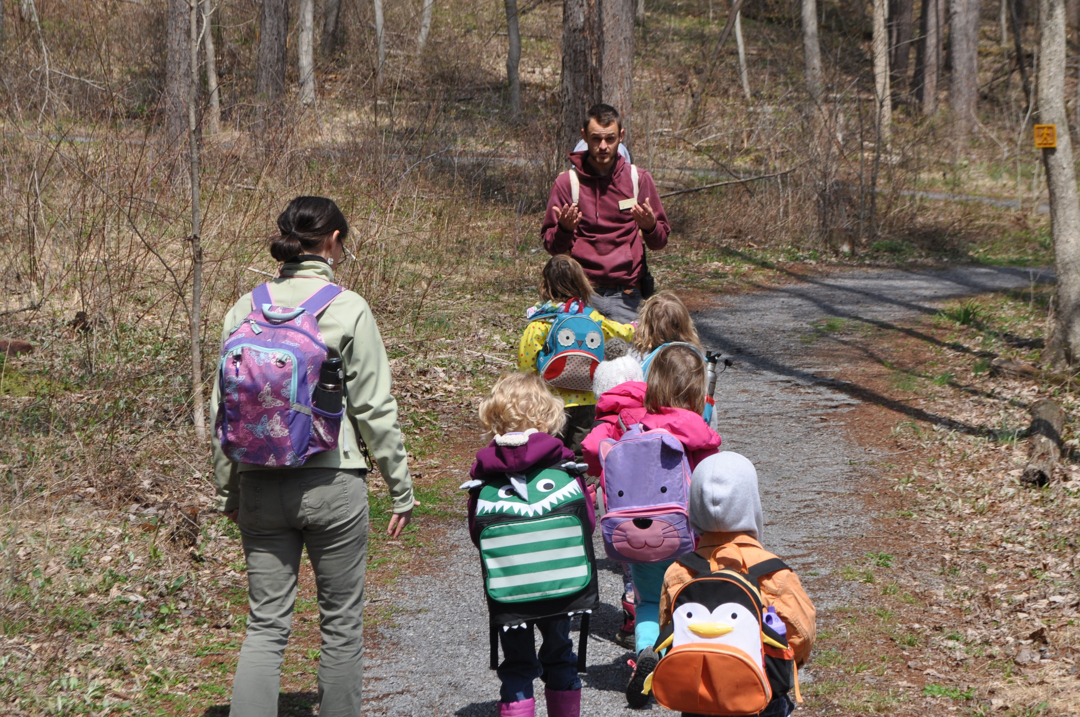Counselor and kids hiking on a trail