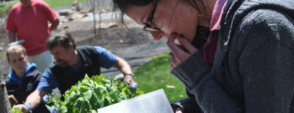 A graduate student references a book as fellow students work in a garden in the background