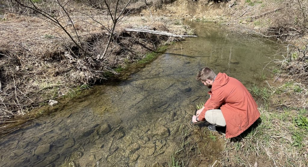 A man taking a water sample from a stream